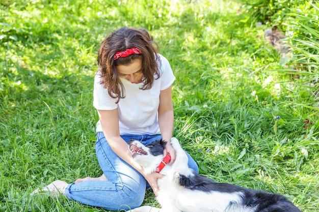 Uśmiechnięta młoda atrakcyjna kobieta bawić się z ślicznym szczeniaka psa border collie w ogródu lub miasta parku
