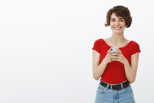 Uśmiechnięta młoda atrakcyjna kobieta sms-y na telefon komórkowy, za pomocą aplikacji randkowej na smartfonie