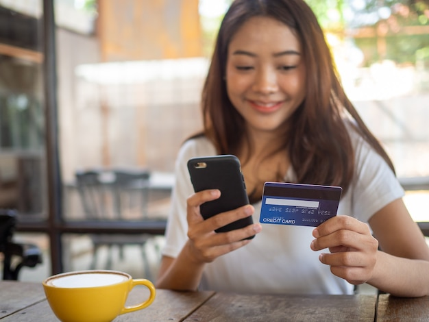 Uśmiechnięta młoda azjatka lubi robić zakupy online za pomocą smartfona i płacić online kartą kredytową. wygoda wydawania bez gotówki. bądź bezpieczny, robiąc zakupy z domu i z odległości społecznej