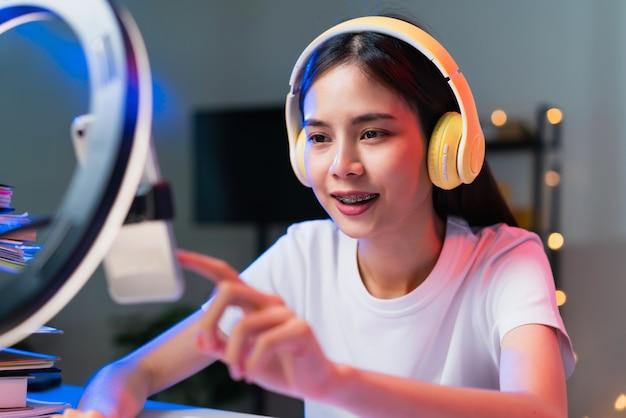 Uśmiechnięta młoda azjatka nosząca zestaw słuchawkowy i transmitująca na żywo w internecie oraz czytająca komentarze z ludźmi w mediach społecznościowych na smartfonie