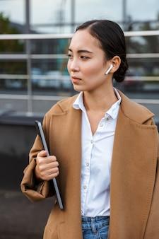 Uśmiechnięta młoda azjatycka bizneswoman w płaszczu, spacerująca po mieście, niosąca laptopa
