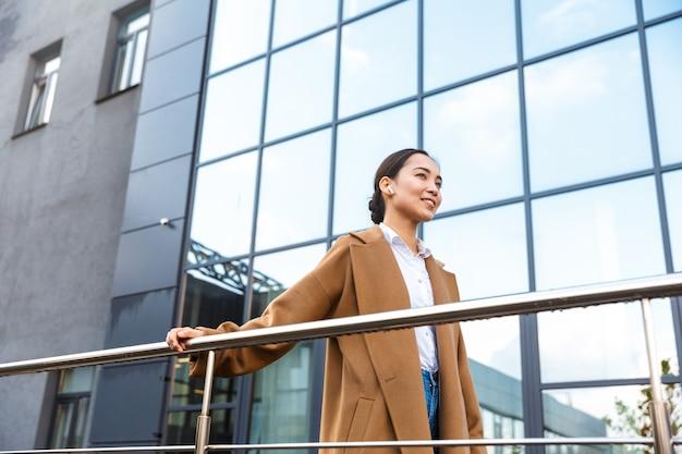 Uśmiechnięta młoda azjatycka bizneswoman w płaszczu stojąca przed szklanym budynkiem na zewnątrz w mieście