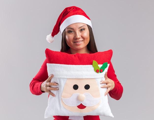 Uśmiechnięta młoda azjatycka dziewczyna nosząca świąteczny kapelusz ze swetrem trzymająca świąteczną poduszkę na białym tle