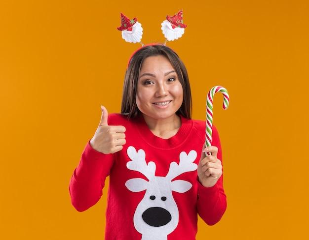Uśmiechnięta młoda azjatycka dziewczyna ubrana w boże narodzenie obręcz do włosów ze swetrem trzyma świąteczne cukierki pokazując kciuk do góry na białym tle na pomarańczowej ścianie