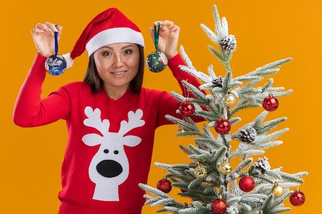 Uśmiechnięta młoda azjatycka dziewczyna ubrana w świąteczny kapelusz ze swetrem stojąca w pobliżu choinki trzymając kulki choinkowe na białym tle na pomarańczowej ścianie