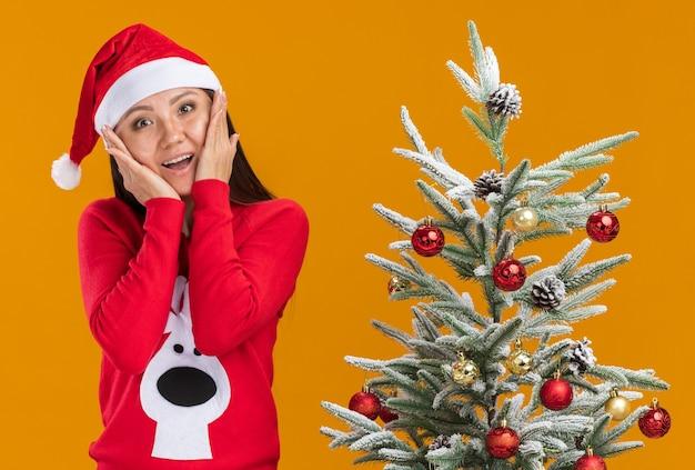 Uśmiechnięta młoda azjatycka dziewczyna ubrana w świąteczny kapelusz ze swetrem stojący w pobliżu choinki kładąc ręce na policzkach na białym tle na pomarańczowym tle