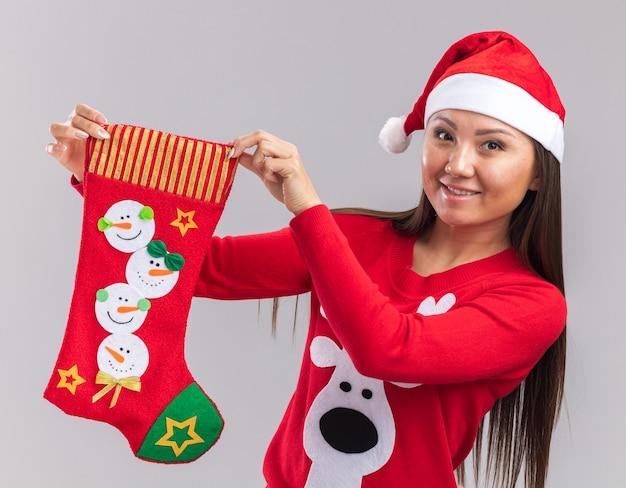 Uśmiechnięta młoda azjatycka dziewczyna ubrana w świąteczny kapelusz ze swetrem trzyma świąteczną skarpetę na białym tle na białej ścianie