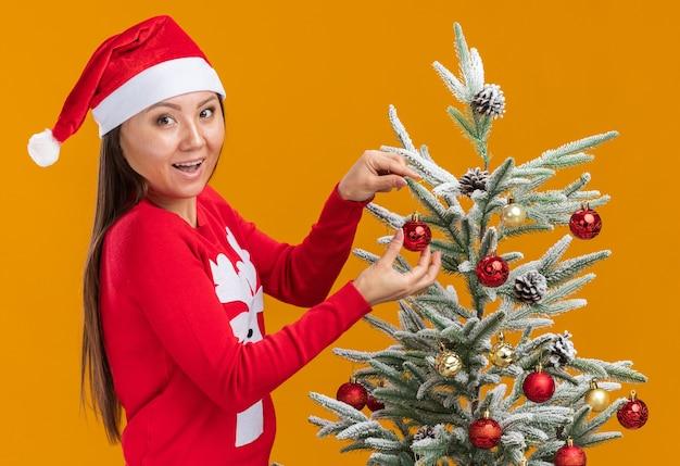 Uśmiechnięta młoda azjatycka dziewczyna ubrana w świąteczny kapelusz ze swetrem udekoruje choinkę na białym tle na pomarańczowej ścianie