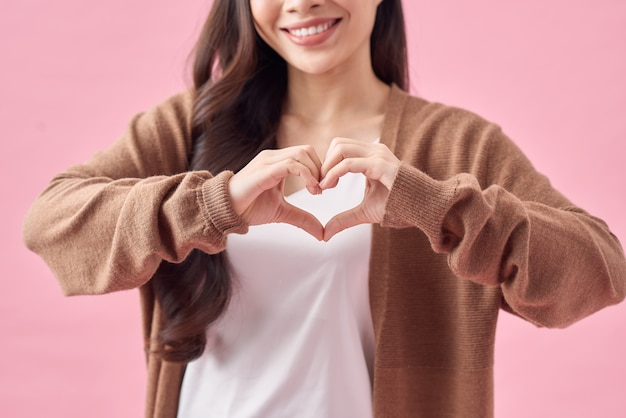Uśmiechnięta młoda azjatycka kobieta pokazująca gest serca dwiema rękami i patrząca na kamerę odizolowaną na różowym tle