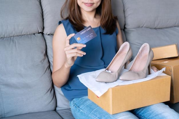 Uśmiechnięta młoda azjatycka kobieta trzyma kartę kredytową podczas gdy patrzejący jej nowego szpilki but i siedzącego na kanapie w domu, cyfrowy styl życia z technologią, e-commerce, robi zakupy online pojęcie
