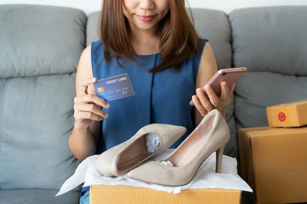 Uśmiechnięta młoda azjatycka kobieta trzyma kartę kredytową podczas gdy trzymający telefon komórkowego i patrzejący jej nowego szpilki but i siedzącego na kanapie w domu, cyfrowy styl życia z technologią, e-handel, zakupy onli