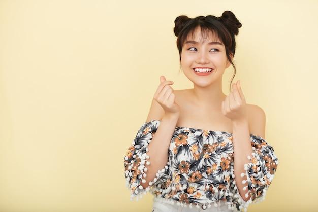 Uśmiechnięta młoda azjatycka kobieta w nagiej naramiennej bluzce pozuje w studiu