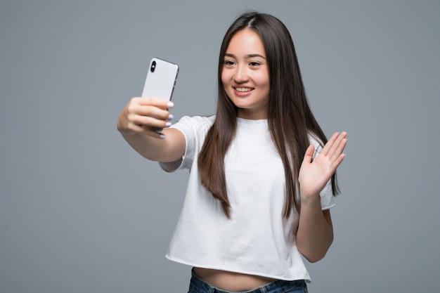 Uśmiechnięta młoda azjatykcia kobieta bierze selfie z telefonem komórkowym nad odosobnionym popielatym ściennym tłem