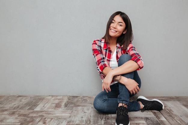 Uśmiechnięta młoda azjatykcia kobieta odizolowywająca nad szarości ścianą.