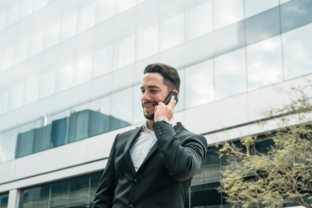 Uśmiechnięta młoda biznesmen pozycja przed budynkiem biurowym opowiada na telefonie komórkowym