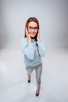Uśmiechnięta młoda biznesowa kobieta na szarej ścianie
