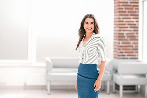Uśmiechnięta młoda biznesowa kobieta stojąca w holu urzędu. zdjęcie z miejscem na kopię