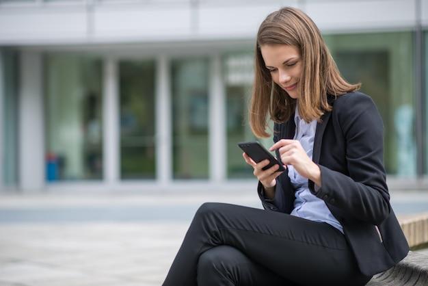 Uśmiechnięta młoda biznesowa kobieta używa jej mobilnego telefon komórkowego