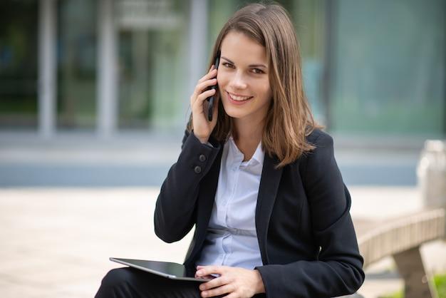 Uśmiechnięta młoda biznesowa kobieta używa swojego telefonu komórkowego