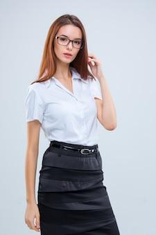 Uśmiechnięta młoda biznesowa kobieta w okularach na szarym tle