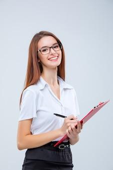 Uśmiechnięta młoda biznesowa kobieta w okularach z piórem i tabletem na notatki na szaro