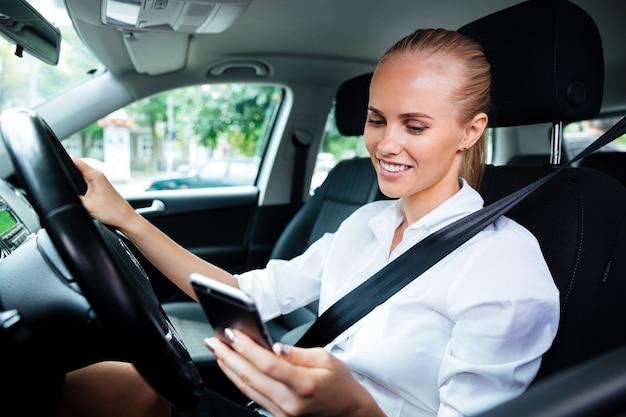 Uśmiechnięta młoda biznesowa kobieta wybiera numer telefonu podczas jazdy samochodem