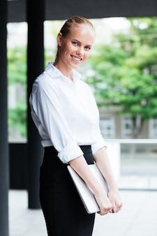 Uśmiechnięta młoda biznesowa kobieta z laptopem stojącym na zewnątrz i patrząca na kamerę