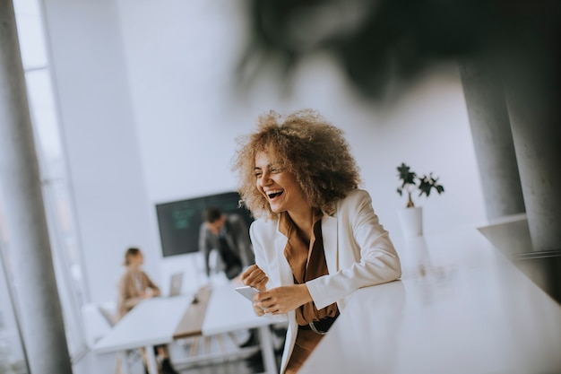 Uśmiechnięta młoda bizneswoman korzystająca z telefonu komórkowego w nowoczesnym biurze
