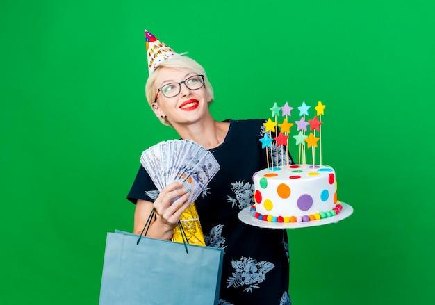 Uśmiechnięta młoda blond kobieta w okularach i czapce urodzinowej trzymająca tort urodzinowy z gwiazdami, pudełko z pieniędzmi i papierową torbę patrząc z boku na zielonej ścianie z miejscem na kopię