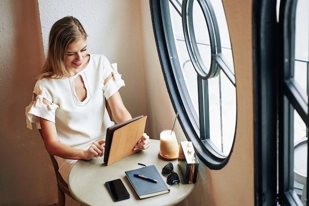 Uśmiechnięta młoda blond kobieta za pomocą aplikacji na komputerze typu tablet, siedząc przy stoliku kawiarnianym