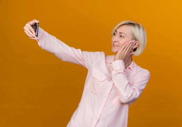 Uśmiechnięta młoda blond słowiańska kobieta bierze selfie i kładąc rękę na policzku na pomarańczowym tle