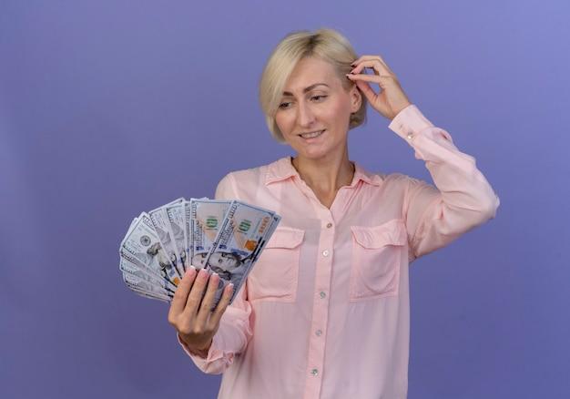 Uśmiechnięta młoda blond słowiańska kobieta, trzymając i patrząc na pieniądze i dotykając włosów na białym tle na fioletowym tle