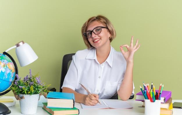 Uśmiechnięta młoda blond studentka w okularach siedzi przy biurku z szkolnymi narzędziami trzymając ołówek, robiąc znak ok