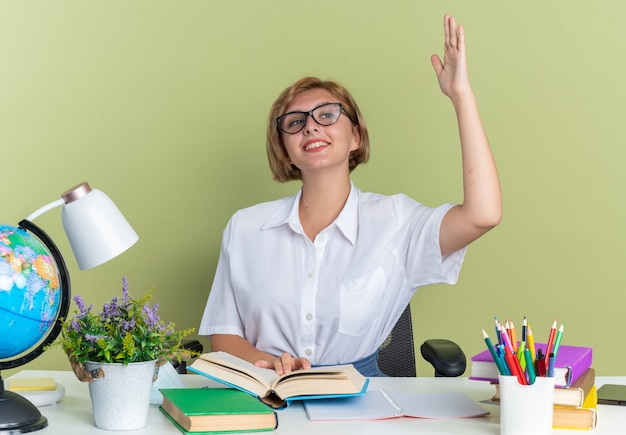 Uśmiechnięta młoda blond studentka w okularach siedzi przy biurku ze szkolnymi narzędziami, trzymając rękę na otwartej księdze, patrząc na bok podnoszący rękę