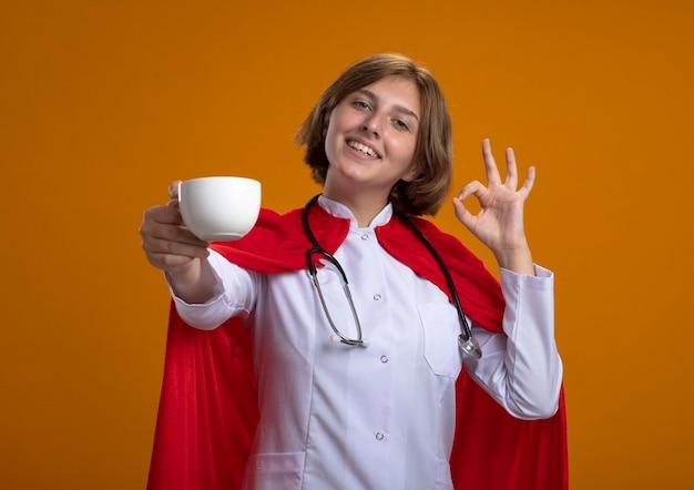Uśmiechnięta młoda blond superbohaterka w czerwonej pelerynie w mundurze lekarza i stetoskopie wyciągająca filiżankę herbaty do przodu, patrząc na przód, robi znak ok na pomarańczowej ścianie