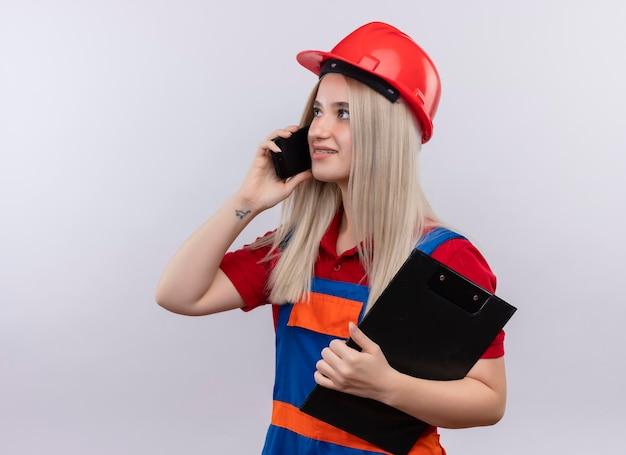 Uśmiechnięta młoda blondynka inżynier budowniczy dziewczyna w mundurze w aparatach ortodontycznych trzymająca schowek i rozmawiająca przez telefon patrząc na lewą stronę na odizolowanej białej przestrzeni z miejscem na kopię