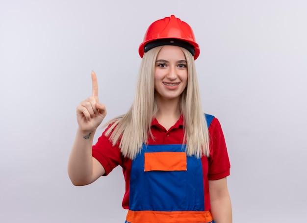Uśmiechnięta młoda blondynka inżynier konstruktor dziewczyna w mundurze w aparatach ortodontycznych podnosząc palec na odosobnionej białej przestrzeni