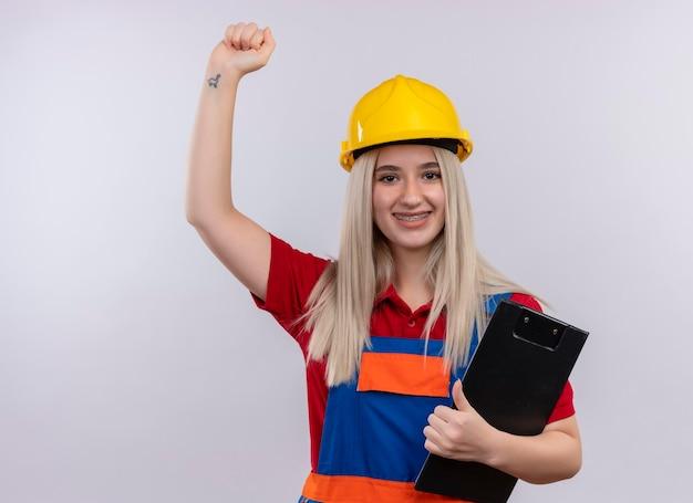 Uśmiechnięta młoda blondynka inżynier konstruktor dziewczyna w mundurze w aparatach ortodontycznych trzymając schowek podnosząc pięść na odizolowanej białej przestrzeni