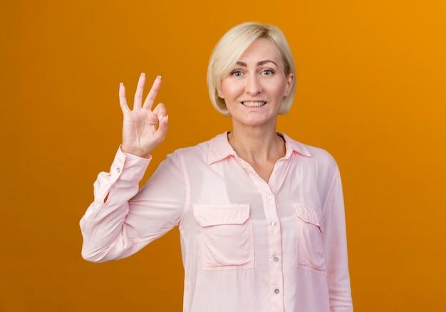 Uśmiechnięta młoda blondynka słowiańska pokazując okey gest na białym tle na pomarańczowej ścianie