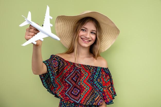Uśmiechnięta młoda blondynka słowiańska w kapeluszu przeciwsłonecznym, trzymająca i patrząca na model samolotu