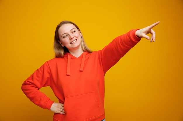 Uśmiechnięta młoda blondynka, trzymając rękę w talii, patrząc i skierowaną w górę w rogu