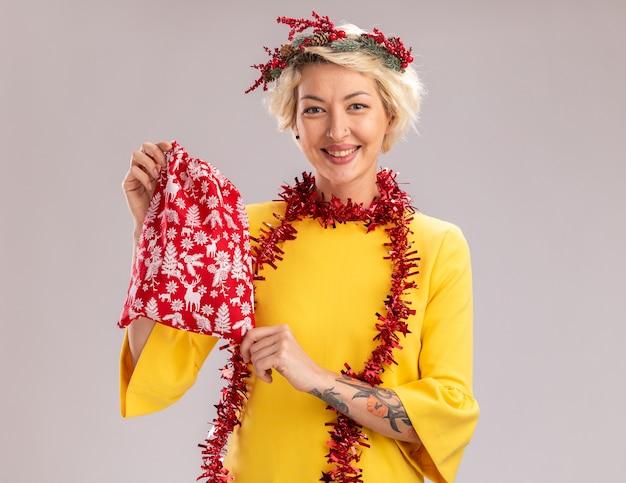 Uśmiechnięta młoda blondynka ubrana w świąteczny wieniec i blichtrową girlandę na szyi trzymającą świąteczny worek na prezenty patrzący na białym tle na białej ścianie