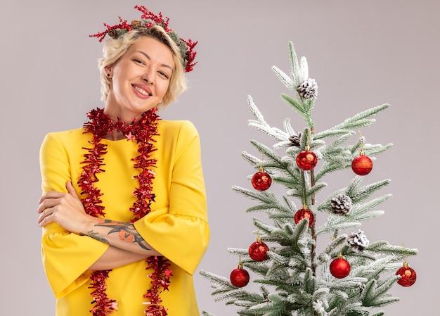 Uśmiechnięta młoda blondynka ubrana w świąteczny wieniec i girlandę ze świecidełek na szyi stojącą z zamkniętą postawą w pobliżu ozdobionej choinki patrzącej na białym tle na białej ścianie