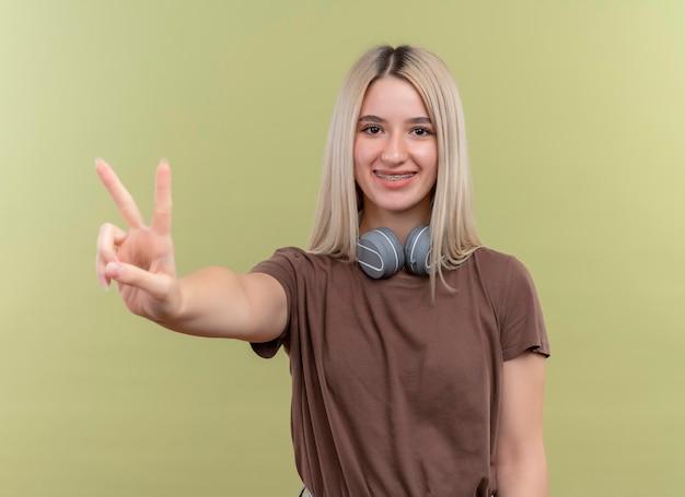 Uśmiechnięta młoda blondynka w aparat ortodontyczny noszenie słuchawek na szyi robi znak pokoju na odosobnionej zielonej przestrzeni