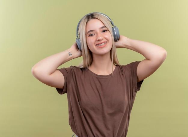 Uśmiechnięta młoda blondynka w aparatach ortodontycznych na sobie słuchawki i kładąc ręce za głowę na odizolowanej zielonej przestrzeni