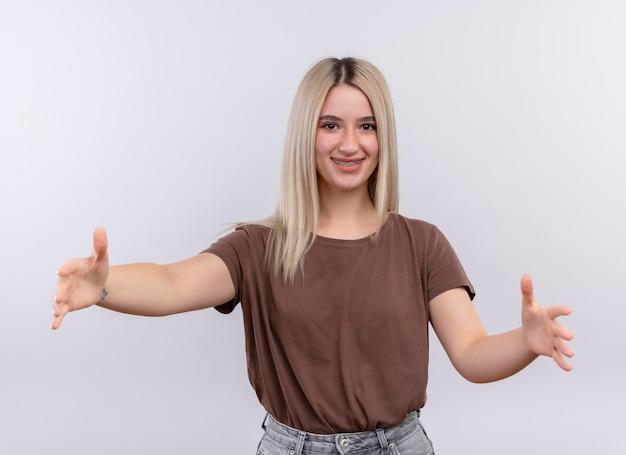 Uśmiechnięta młoda blondynka w aparatach ortodontycznych udawać, że trzyma coś na odosobnionej białej przestrzeni