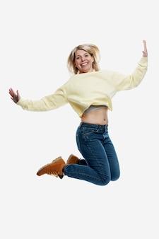 Uśmiechnięta młoda blondynka w dżinsach i żółtym swetrze skacze. aktywność i pozytywne nastawienie. pojedynczo na białym tle. pionowy.