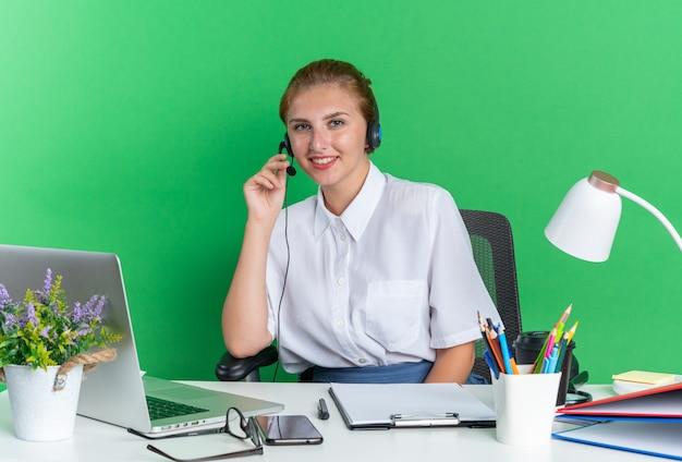 Uśmiechnięta młoda blondynka z call center w zestawie słuchawkowym siedząca przy biurku z narzędziami do pracy chwytającymi mikrofon zestawu słuchawkowego