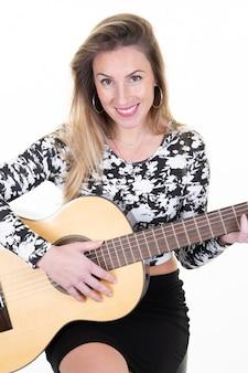 Uśmiechnięta młoda blondynki dziewczyna bawić się gitary obsiadanie odizolowywającego na białym tle