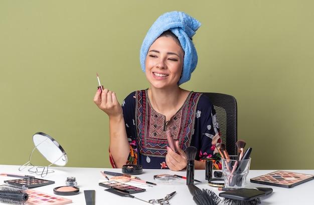 Uśmiechnięta młoda brunetka dziewczyna z owiniętymi włosami w ręcznik, siedząca przy stole z narzędziami do makijażu trzymającymi błyszczyk